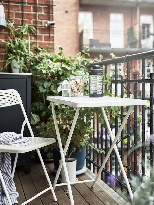A small balcony with a white/beige TORPARÖ table and folding chair, potted plants, a glass of water and floor decking.
