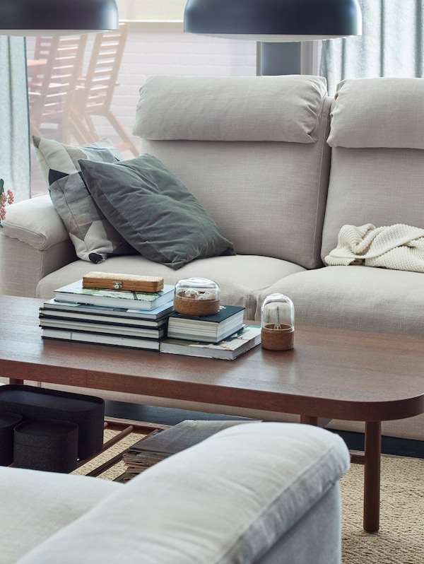 IKEA LIDHULT light beige sofas facing a dark brown coffee table.