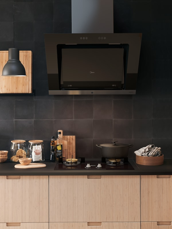 A kitchen cooking area with UPPSVING extractor hood in black and an EKBACKEN counter top.
