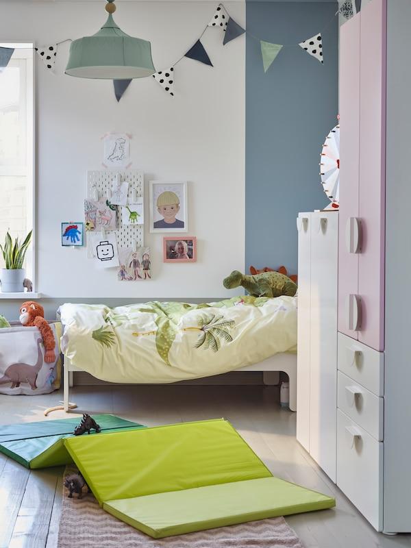 Naast een SLÄKT uitschuifbaar bed staat een SMÅSTAD opberger in een kinderkamer. Op de grond ligt een PLUFSIG opvouwbare gymmat.