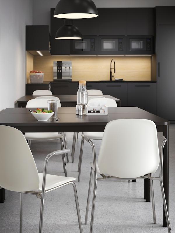 Due gruppi di tavoli da cucina antracite con sedie bianche, in una cucina con frontali scuri e un aspetto pulito - IKEA
