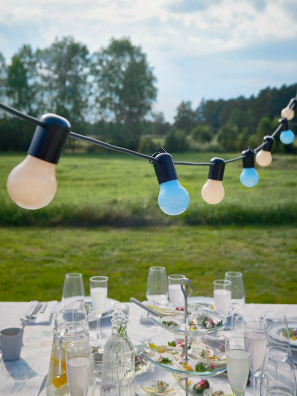 A colourful SOLVINDEN LED lighting chain hangs over a table set with food and drinks for an outdoor wedding reception.