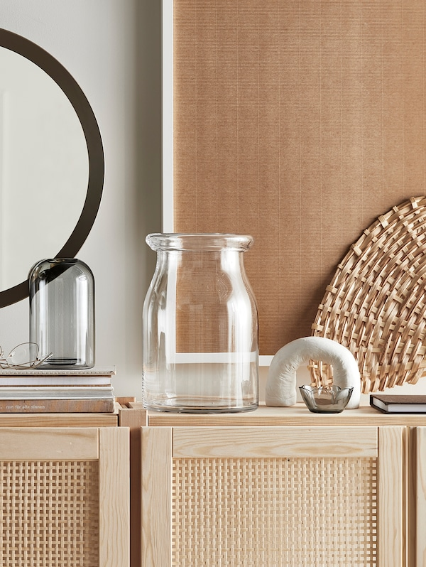 Wooden storage units with glass vases on the top, and various other items like a small glass dish and a notebook.