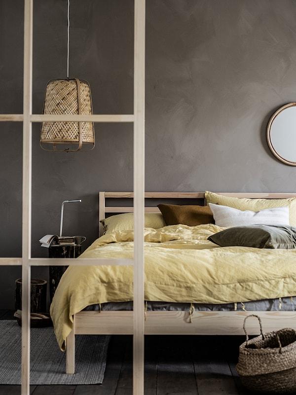 Chambre zen avec lit double et linge de lit jaune clair