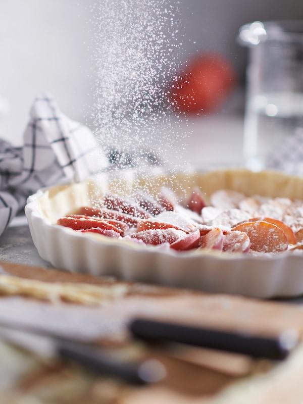 Eine Arbeitsplatte mitten in einer Backsession. Puderzucker rieselt auf eine VARDAGEN Form mit Pfirsichkuchen herab.