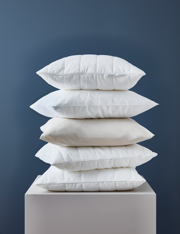 A pile of FÄRGMÅRA pillows with DVALA pillowcases