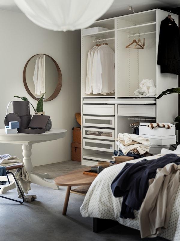 Otwarta szafa PAX z szufladami i ubraniami zawieszonymi na drążkach, ustawiona pod ścianą sypialni w pobliżu białego stołu.