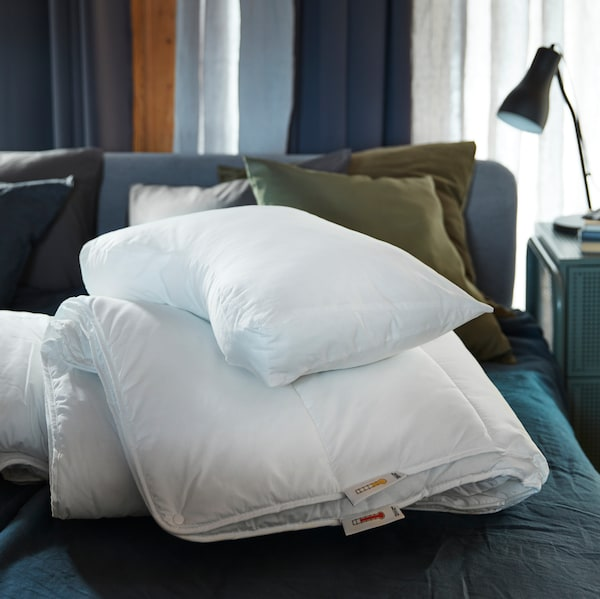 A bed with blue bed linen, a white duvet, a white SKOGSLÖK ergonomic pillow and green cushions in the background.