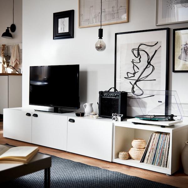 Armário de TV branco BESTA com puxadores pretos junto a uma parede decorada com molduras pretas.