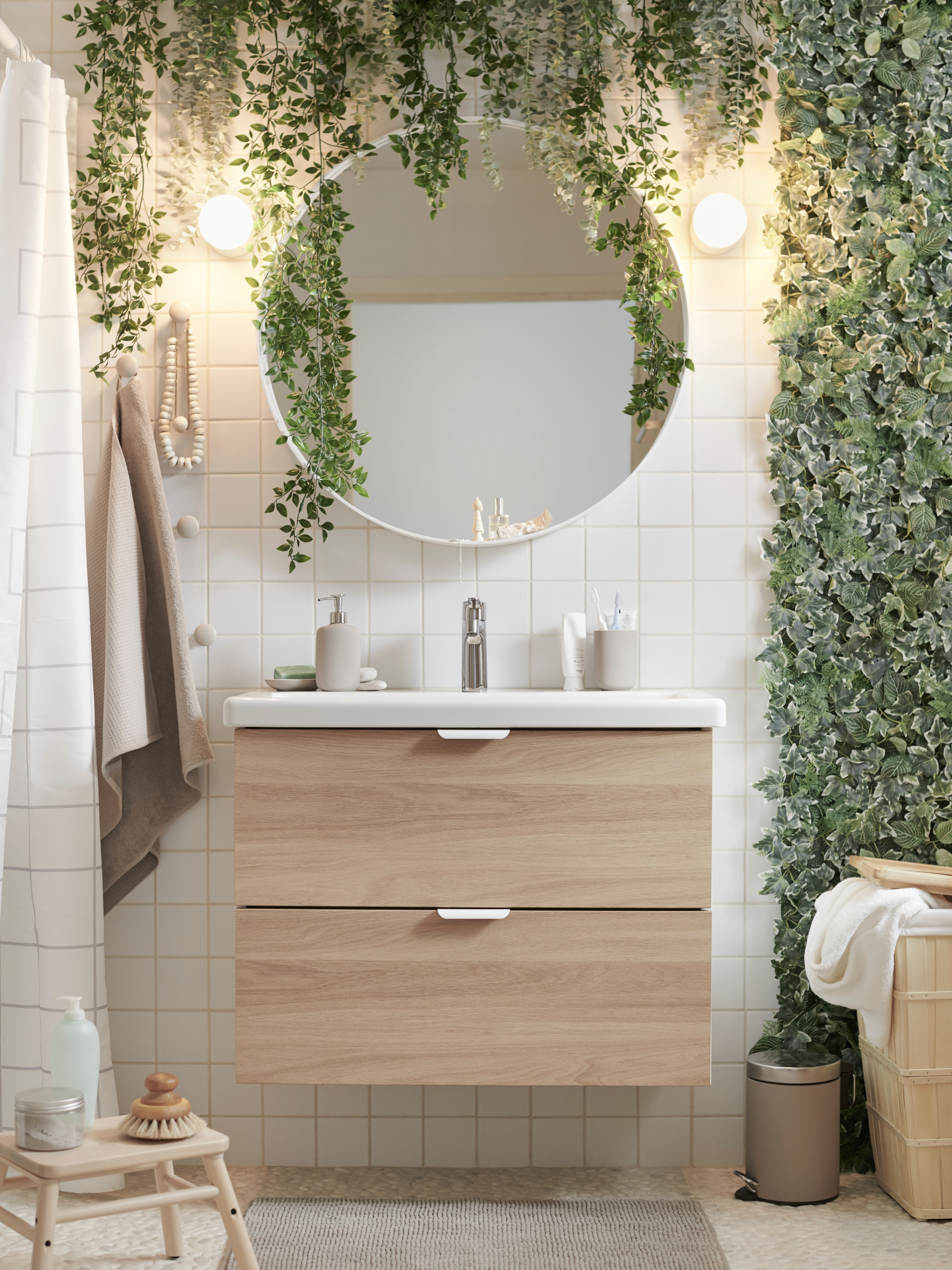 A bathroom decorated with FEJKA artificial plants, an ENHET/TVÄLLEN wash-stand with wooden drawer fronts and a round mirror.