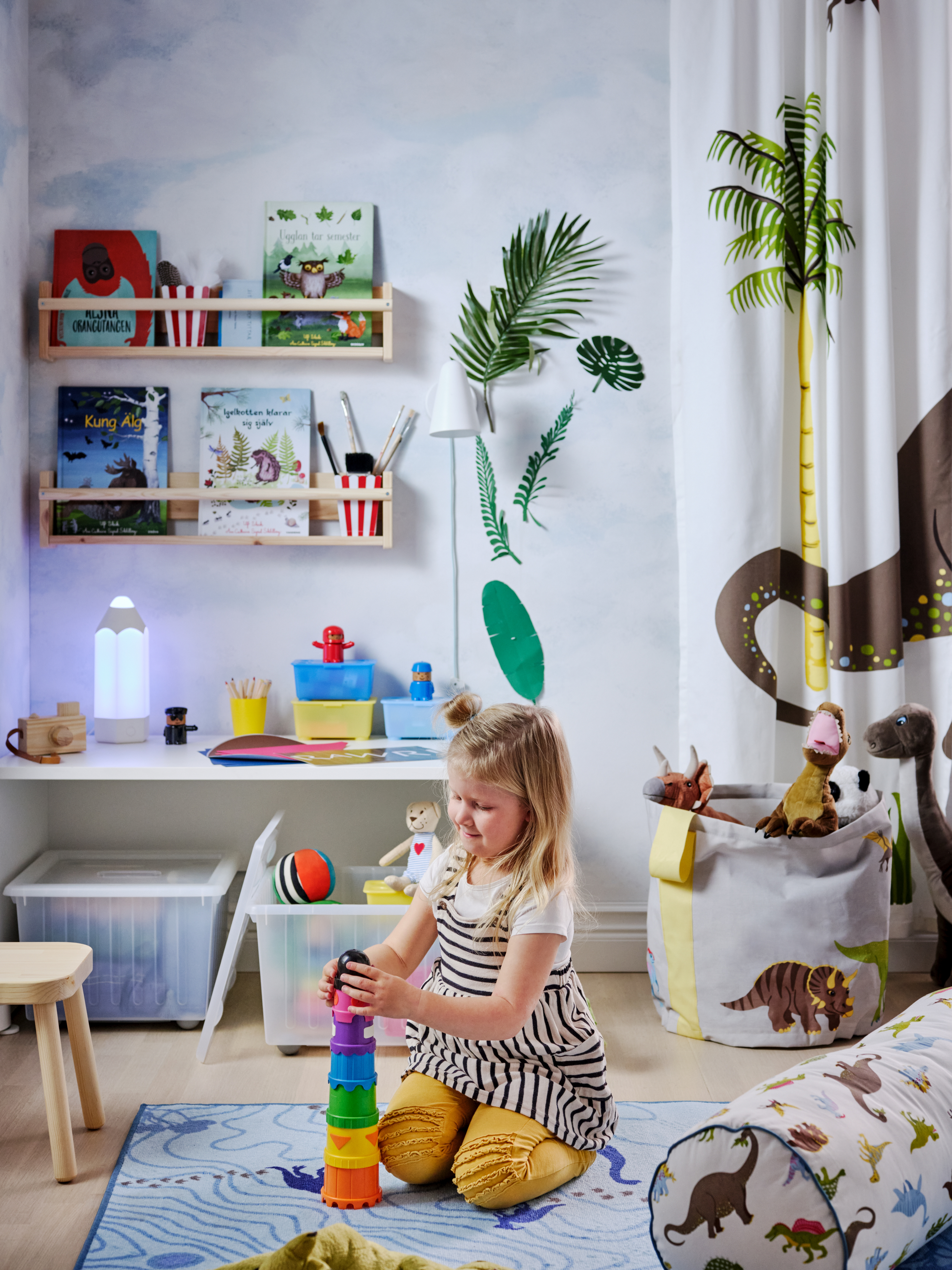 A girl plays with coloured blocks in a dinosaur-themed room. More toys are kept in VESSLA boxes and a JÄTTELIK bag.
