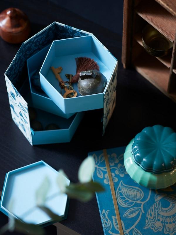 桌上放着ANILINARE 安妮丽娜睿 系列蓝色储物盒,装着各式小物件和其他文具产品。