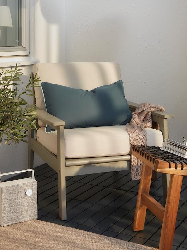 BONDHOLMEN Sessel mit blauem GULLINGEN Kissen auf einem Balkon