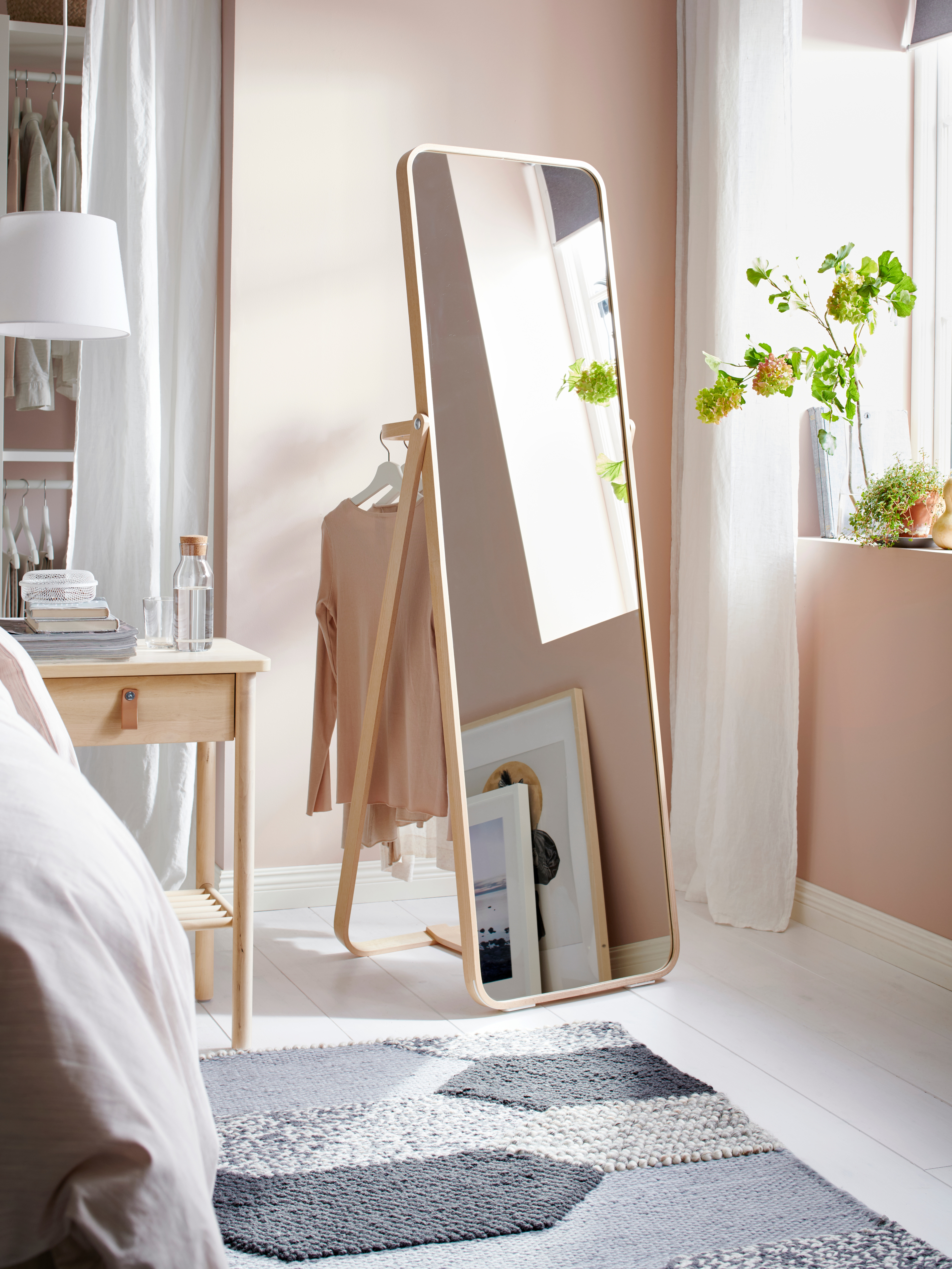 An ash IKORNNES standing mirror has a sweater hanging on its attached back rail, facing a window in an airy, pink bedroom.
