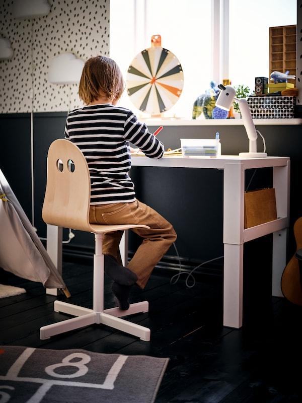 Ein Kind sitzt an einem weißen Schreibtisch.