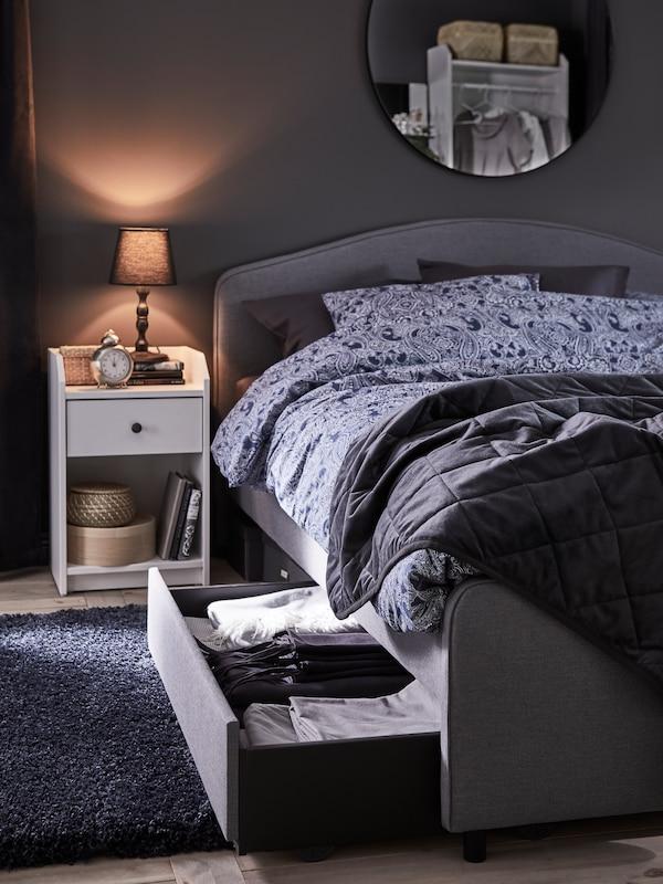 En grå HAUGA polstret seng med en opbevaringsskuffe trukket ud og et sengebord ved siden af med en lille bordlampe på.