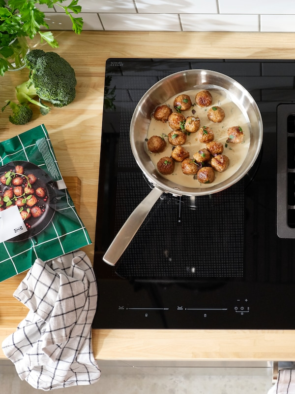A frying pan cooking plant balls on an induction cooktop.
