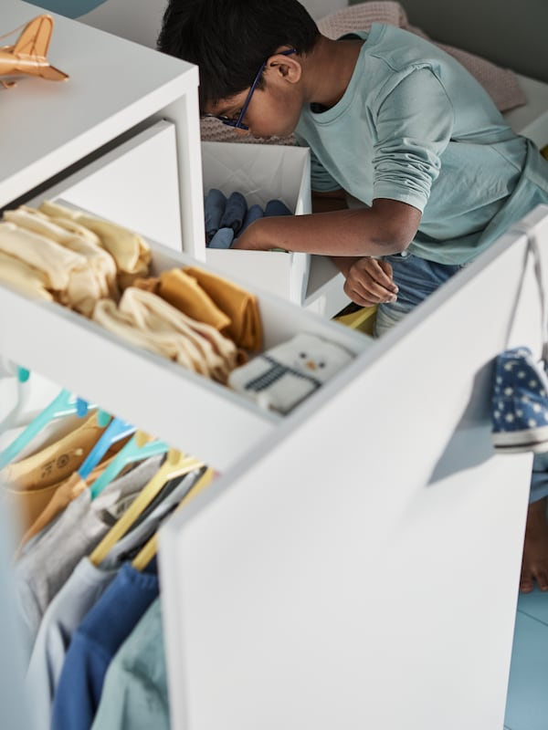 A boy looking for clean socks in a white box beside an open, white SMÅSTAD wardrobe with pull-out unit filled with clothes.