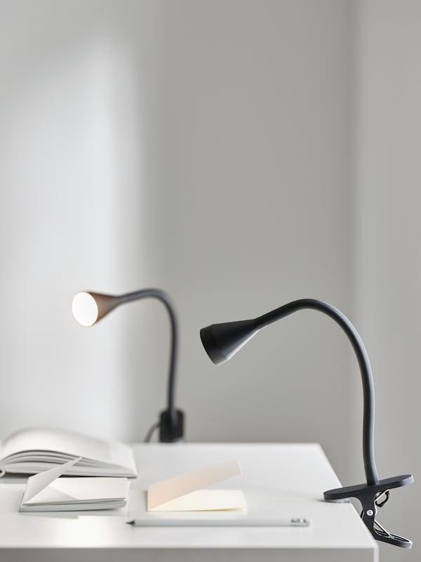 Dua lampu sorot LED NÄVLINGE berpengapit berwarna hitam disepit kepada meja berwarna putih yang terdapat buku dan pensil.