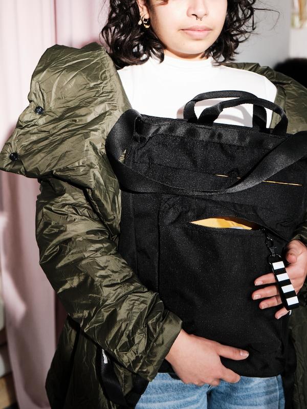 Une jeune femme portant un chandail et un manteau d'hiver vert qui tient un fourre-tout de voyage noir VÄRLDENS lourd de 16L avec des fermetures à glissière ouvertes.