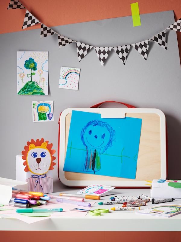 На столе лежат фломастеры и сумка-планшет для рисования из серии МОЛА, на планшете рисунок. Позади на стене тоже висят рисунки.
