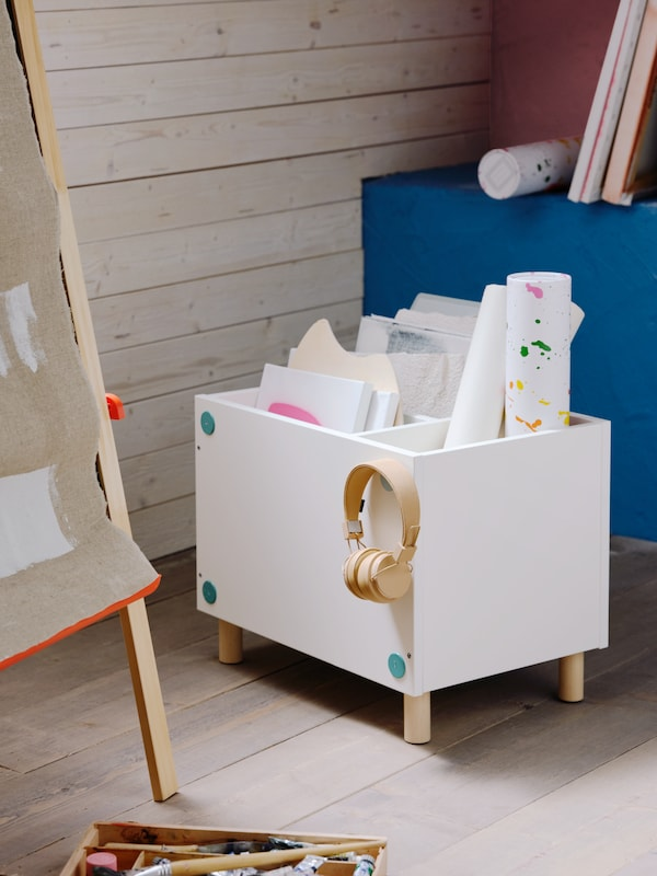 A children's room with a white SMUSSLA bedside table/shelf unit used as storage for drawings and hanging earphones.