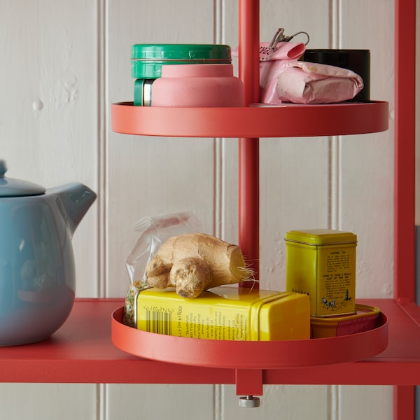 A red-orange ENHET swivel shelf filled with small cans and containers, fastened to an ENHET shelf with a blue tea pot.