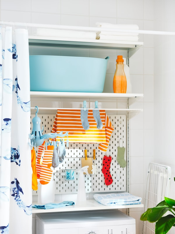 A laundry area with a TORKIS flexi laundry basket, a SKÅDIS pegboard, a hanger with pegs and laundry on a BOAXEL shelf unit.