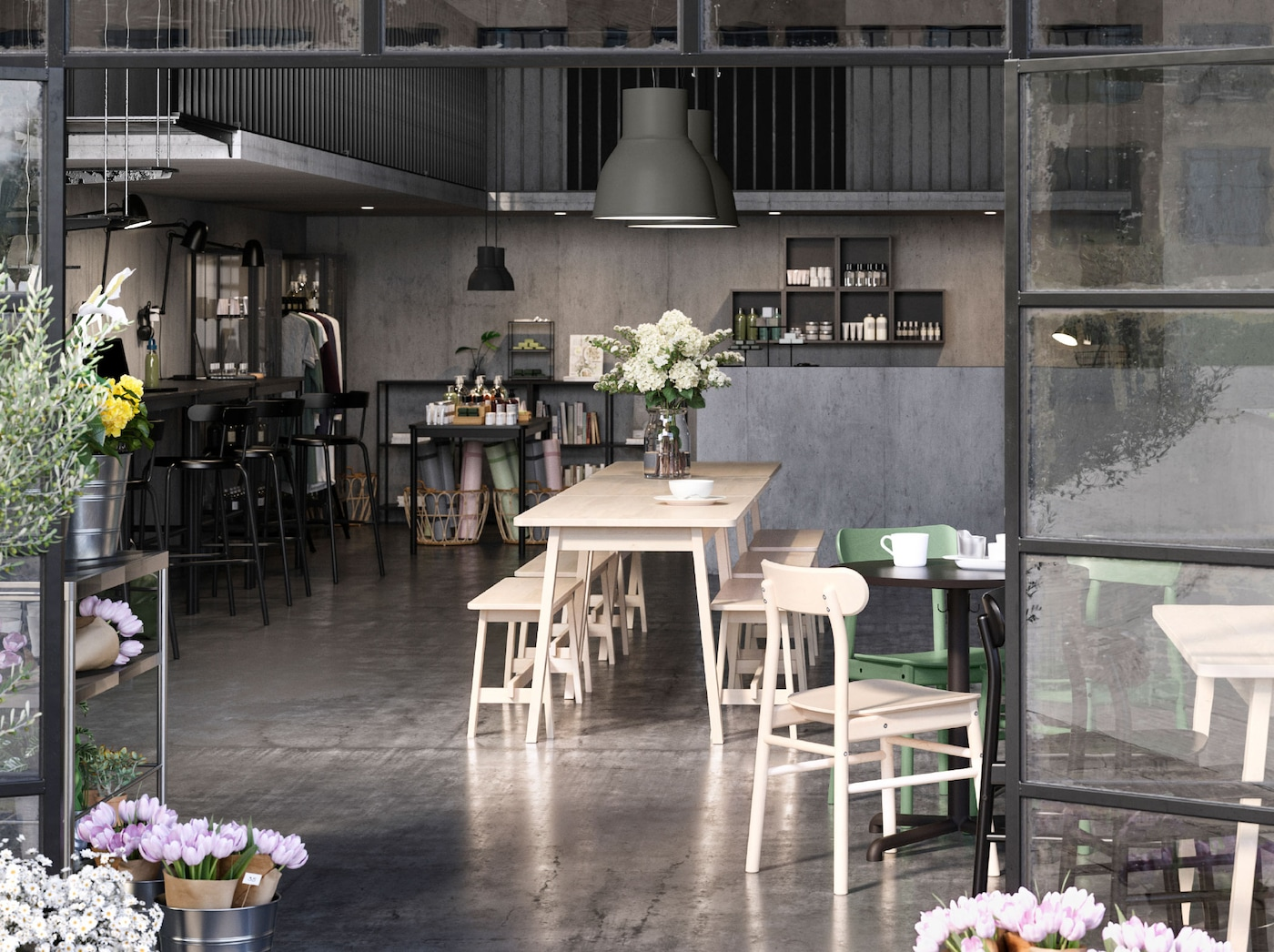 열린 유리도어가 프레임을 이룬 오픈 플랜식 구조의 카페, 매장과 공동 업무공간. 꽃이 도어 옆 테이블에 놓여 있는 모습.