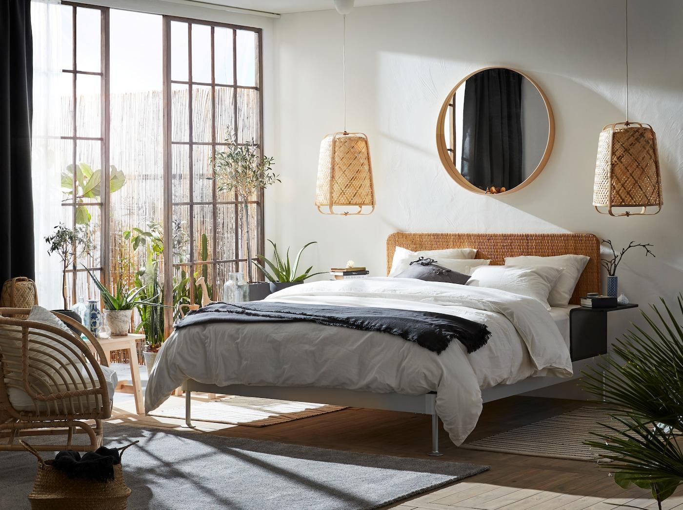 라탄과 대나무 같은 천연 소재를 다양하게 활용해 화사하게 꾸민 침실, 침대 옆으로 보이는 큰 유리 도어와 야외 공간