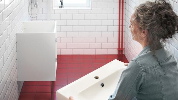 화이트와 레드 타일의 욕실에서 화이트 세면기를 잡고 벽에 고정된 화이트 하부장을 보고 있는 여성.