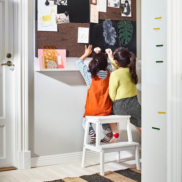 여자아이 두명이 함께 화이트 스텝스툴에 앉아 벽을 꾸미고 있어요.