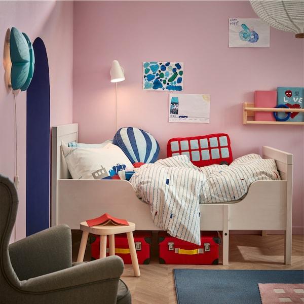 화이트 색상의 길이조절 어린이 침대프레임 위에 보트 패턴이 그려진 침구가 있고, 그 위로 화이트 벽등이 켜져 있는 모습