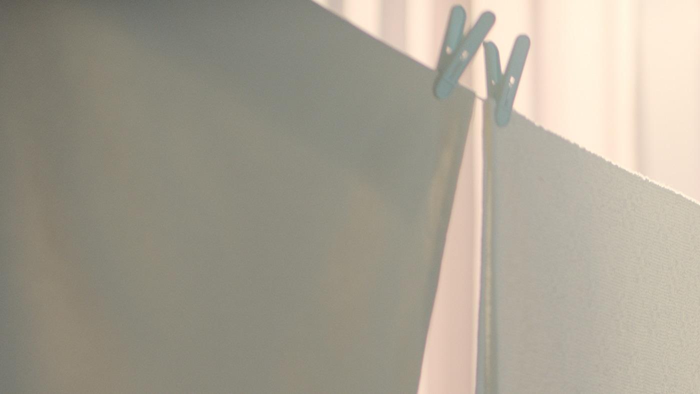 빨랫줄에 걸린 화이트 색상 텍스타일 세 개와 핑크 색상 텍스타일 한 개, 배경으로 브라운 색상의 점퍼를 입은 사람의 팔과 상체가 보이는 모습.