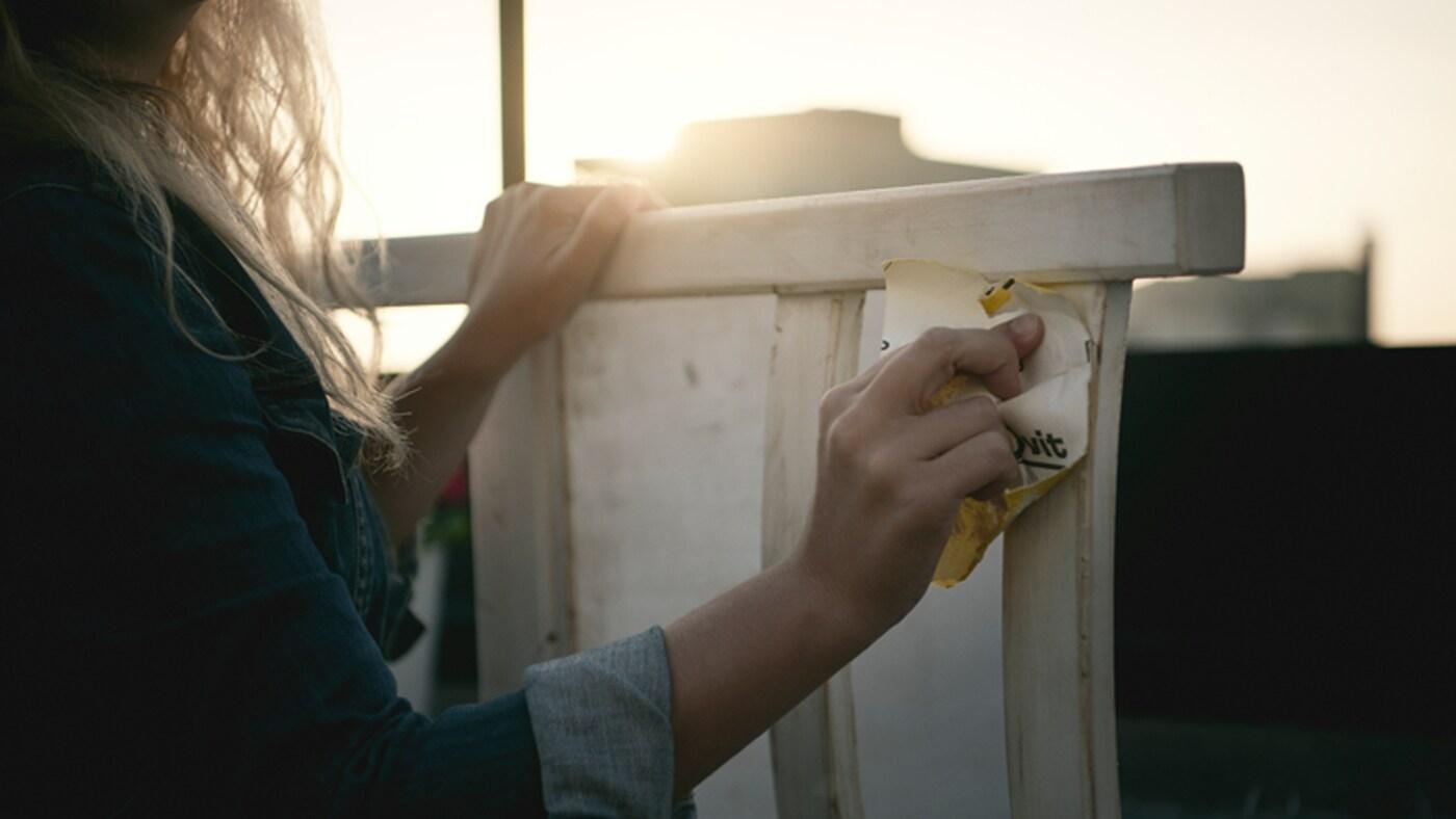 한 여성이 목재 가구에 백색 도료를 바르고 있는 모습. 배경에는 태양이 밝게 빛나고 있어요.