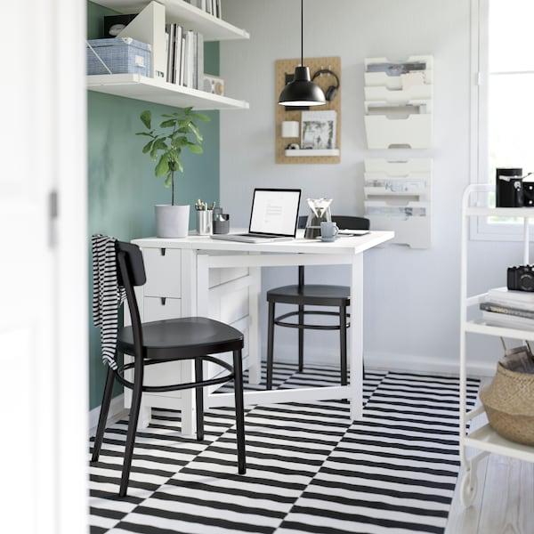 화이트 노르덴 테이블을 중심으로 블랙 색상의 의자 두 개가 놓여있고, 테이블 위에는 노트북이 있어요.