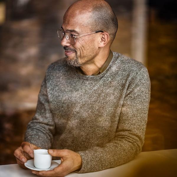 안경을 낀 중년 남성이 커피를 즐기며 웃고 있네요.
