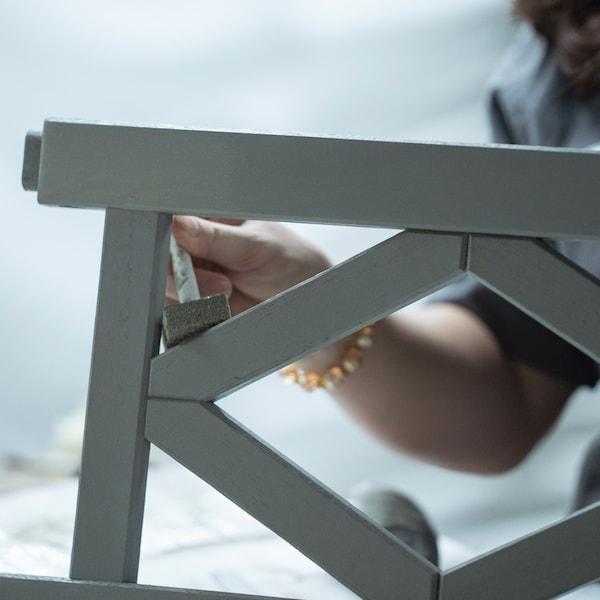 그레이 야외용 의자의 측면 팔걸이에 폼브러시로 페인트칠을 하는 손.