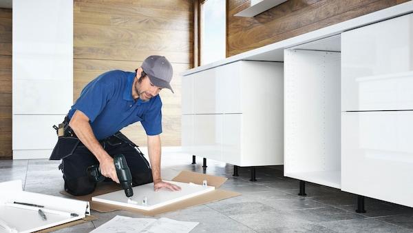 파란옷을 입은 남성이 전동 공구를 사용해 주방 가구를 조립하고 있는 모습