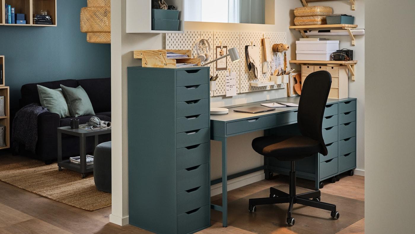 거실과 업무 공간을 분리해 놓은 벽, 그레이터쿼이즈 책상과 서랍유닛, 블랙 사무용 의자.