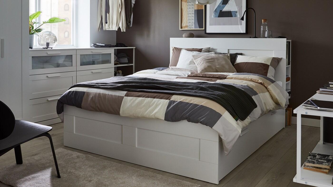 เตียงสีขาวพร้อมหัวเตียง ปลอกผ้านวมและปลอกหมอนมีลวดลายสีน้ำตาล ผ้าคลุมสีเทา และหมอนอิงสีขาว สีเทา และสีเบจ