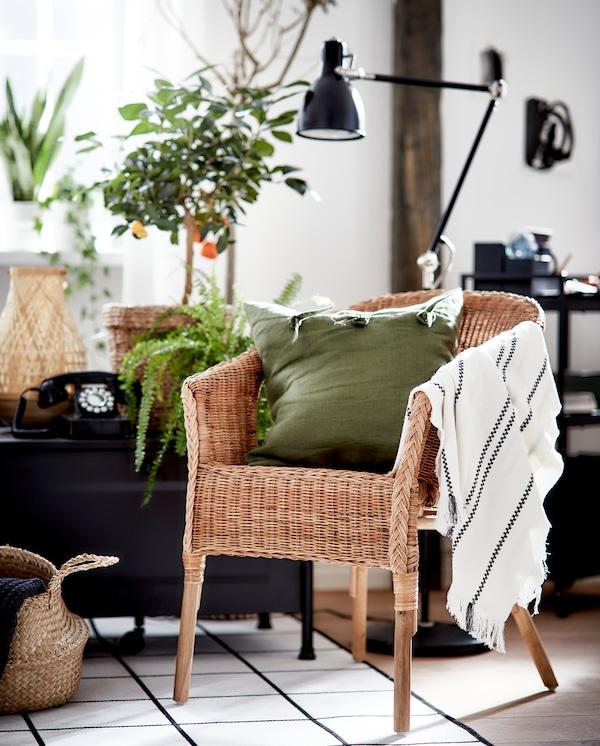 그린 쿠션과 줄무늬 담요가 놓여 있는 라탄/대나무 의자, 블랙/화이트 러그, 블랙 플로어스탠드, 잘피 바구니가 어우러진 모습.