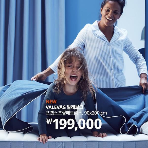 매트리스 위에서 웃고있는 어린이와 뒤에서 시트를 펼치고 있는 여성