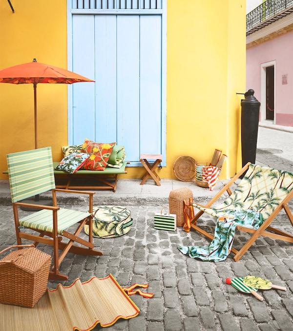 그린 색상의 패턴과 프린트가 돋보이는 접이식 흔들의자와 안락의자가 자갈길 바닥 위에 놓여 있는 모습.
