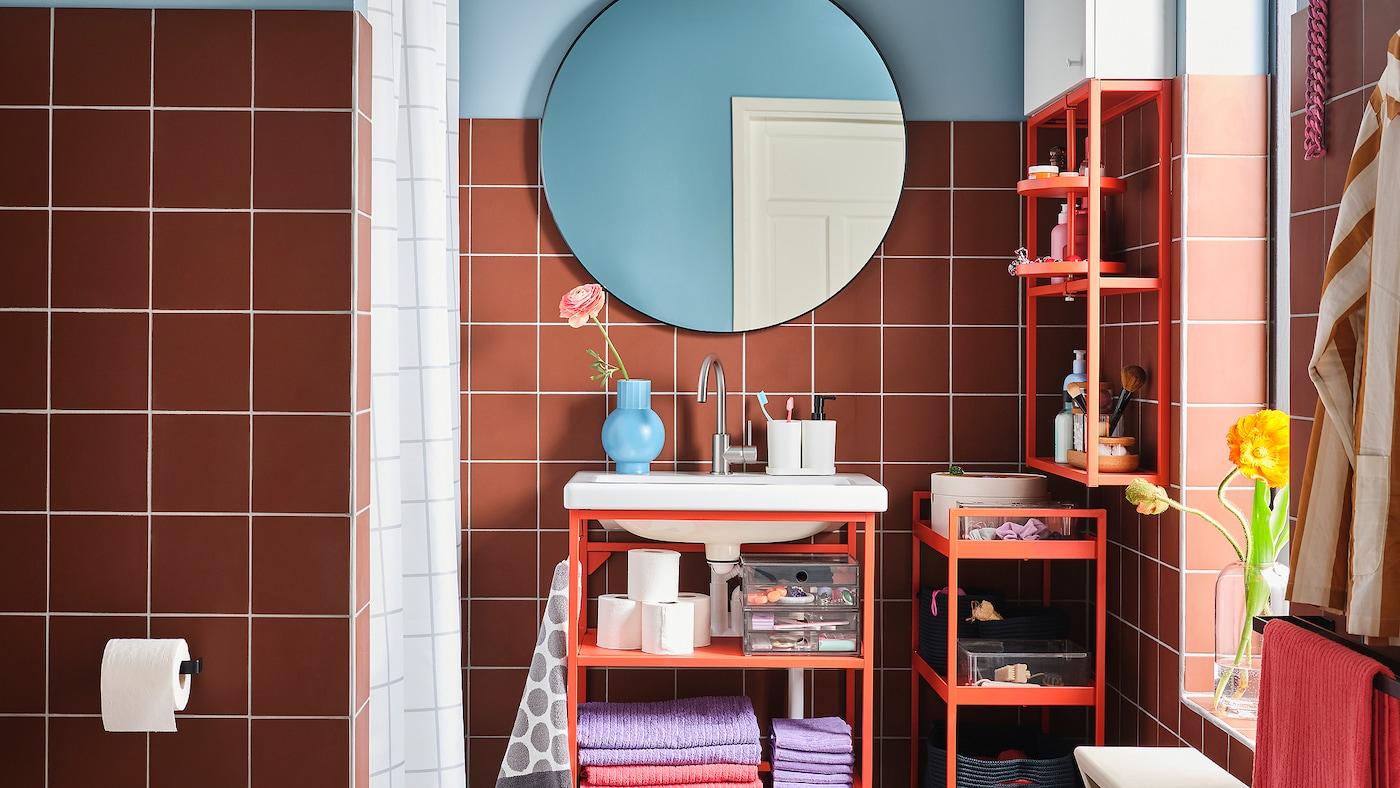 ห้องน้ำสีสันสดใสพร้อมอ่างล้างหน้า ชั้นวางของ และรถเข็นเหล็กสีแดงส้ม และกระจกทรงกลม