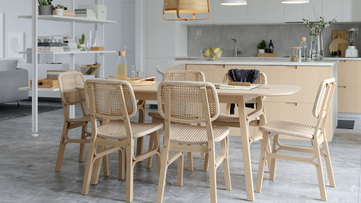 대나무와 종이로 엮은 스타일의 식탁과 의자, 화이트 실내칸막이, 주방 아일랜드로 꾸민 밝은 분위기의 다이닝 공간.