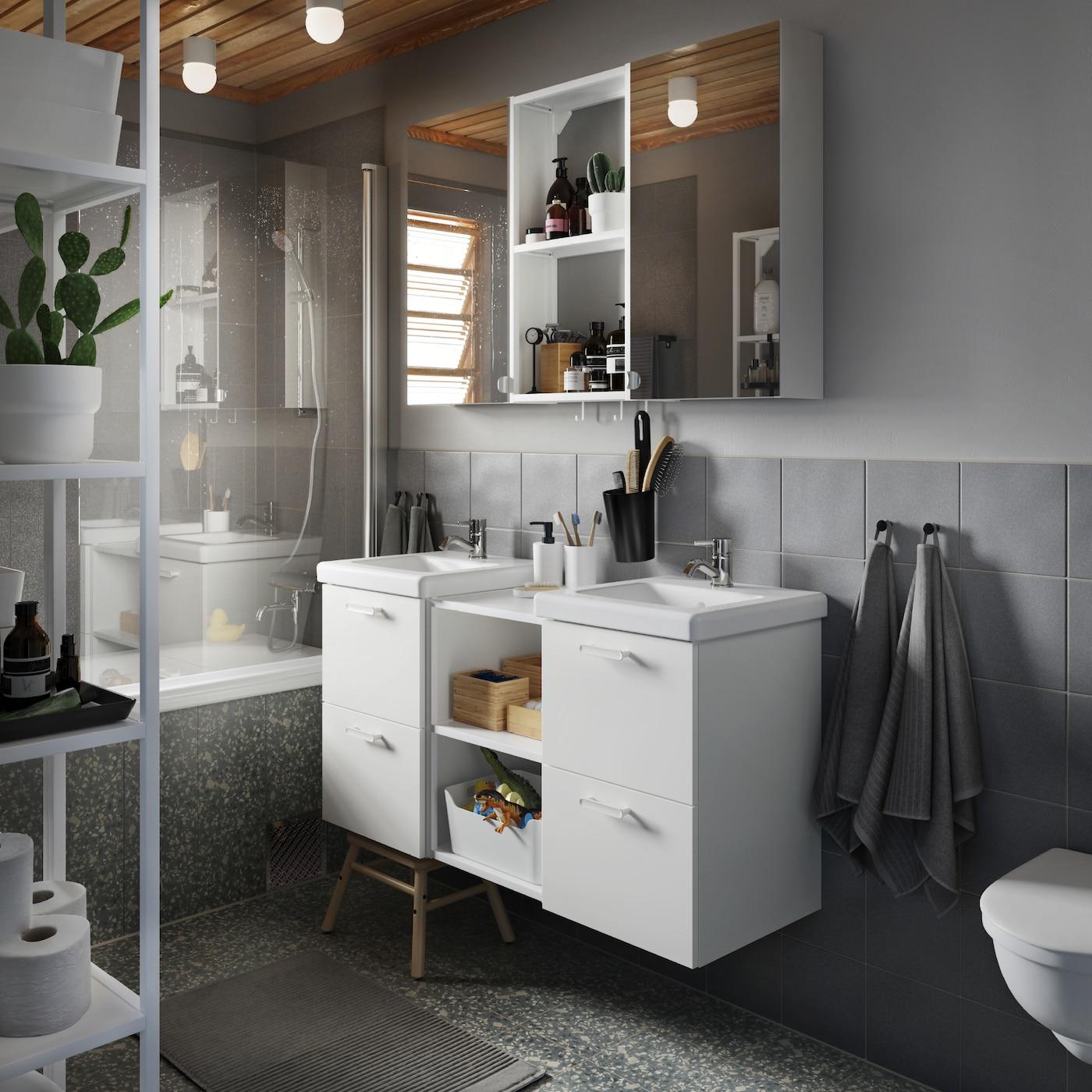 ห้องน้ำสีเทาและตู้ตั้งอ่างล้างหน้า/อ่างล้างหน้าสีขาว ตู้พร้อมบานตู้ติดกระจกเงา รวมทั้งผ้าเช็ดตัวและพรมห้องน้ำสีเทา