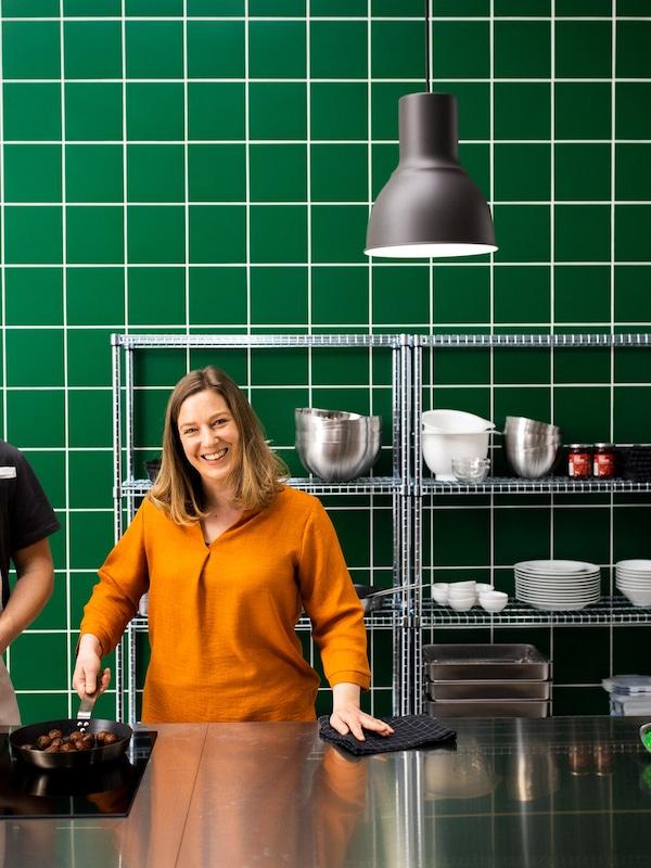 ผู้หญิงยืนอยู่ในครัวที่ตกแต่งด้วยสเตนเลสและผนังกระเบื้องสีเขียว ถือกระทะสำหรับทอดในกระทะมีมีทบอลทำจากผัก