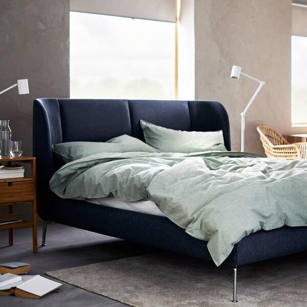 เตียงสีน้ำเงินเข้มกับชุดปลอกหมอนและผ้านวมสีเขียวอ่อน