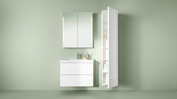 Ein beige gestrichener Raum, in dem nur ein Waschbeckenschrank, ein Spiegelschrank und ein Hochschrank in Weiß an der Wand befestigt zu sehen sind.